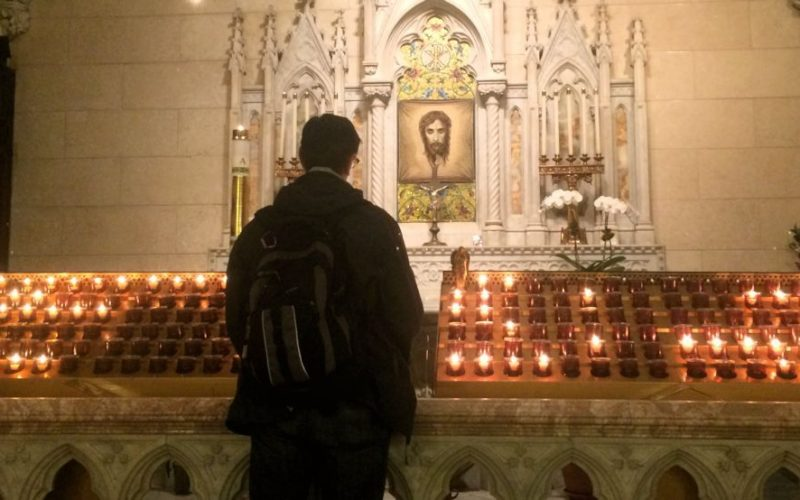Man praying at votive candles