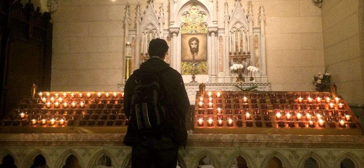 Man praying at votive candles